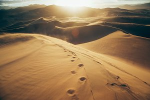 Sunset with footsteps in sand dunes