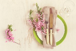 Spring table setting with sprigs of flowering almonds, tinted