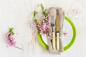 Spring table setting with sprigs of flowering almonds. Celebrato