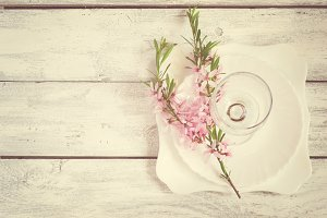 Spring table setting, white plate and wine glass decorated with