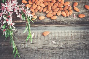 Almond nuts scattered on the old wooden background, tinted. Top