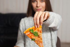 Woman keeps a slice of pizza