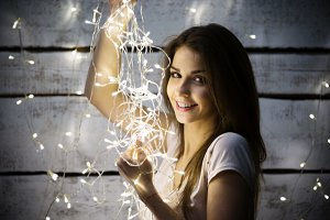 Portrait of beautiful brunette woman holding glowing christmas garland in hands
