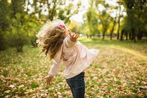 Happy child girl having fun in autumn park