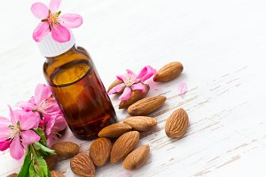 essential almond oil, almonds and flowers. Top view with copy sp
