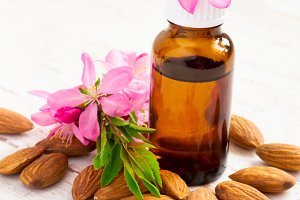essential almond oil, almonds and flowers