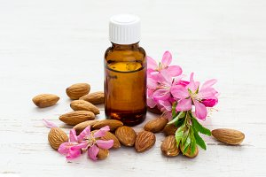 small bottle of almond oil, almonds and flowers