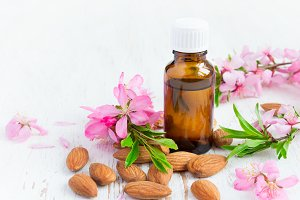 Essential almond oil, flowers and nuts on a white background