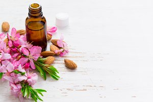 Spa background with almond essential oil and flowers