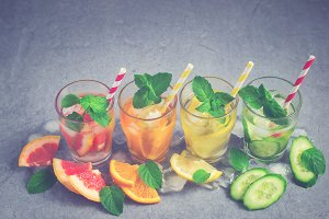 Refreshing summer drinks water with ice and lemon, orange, grape
