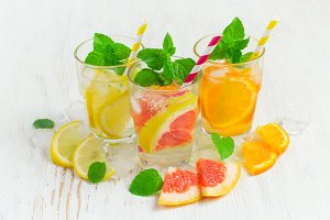 Refreshing summer drinks water with ice and lemon, orange  and