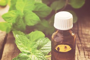Essential oil of peppermint in a small bottle with fresh mint, s