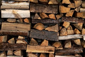 Dry Firewood neatly stacked in the woodpile. Background.