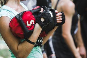 Close-up of woman training at crossfit center with sandbag