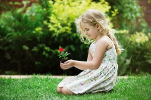 Little blonde girl holding young flower plant in hands on green background