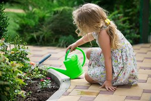 Cute little girl watering plants in the garden