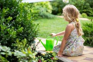 Cute little girl watering plants in the garden