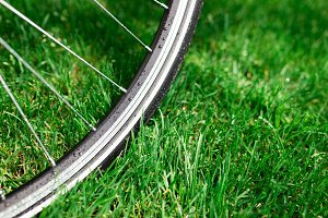 Classic road bicycle wheel close-up photo in the summer green grass meadow field. Travel background