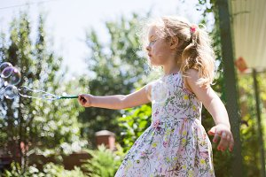 Cute little girl is blowing a soap bubbles and having fun