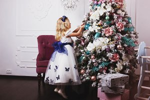 Little blonde girl in beautiful dress decorating Christmas tree at home