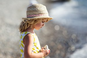 Cute little girl in yellow dress and straw hat standing barefoot on waves along the beach in a summer sunny day.