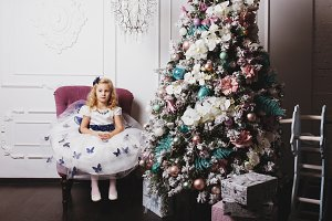 Little blonde girl in beautiful dress waiting for gifts sitting near Christmas tree at home