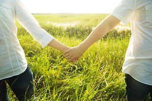 Couple holding hands with romantic view at the sunlit field