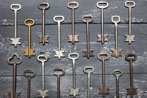 Some door keys aligned on old wooden surface, safety and security concept background