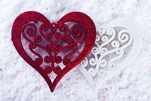two red wooden heart on white snow