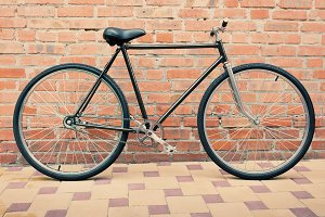 Retro style bicycle against brick wall, vintage tinted photo