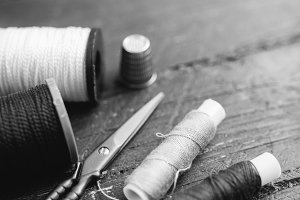 Sewing accessories: bobbins of thread, scissors, needle, thimble on wooden table. Black and white photo. Tailoring and sewing concept.