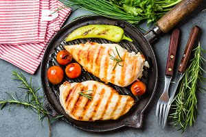Grilled chicken fillets, chili and tomatoes on grill iron pan
