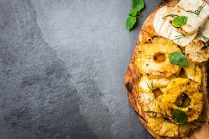 Grilled pineapple slices, fresh cheese with mint, olive cutting board