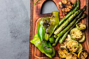 Grilled green vegetables zucchini, asparagus, bell pepper on wooden board