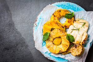 Grilled pineapple slices, fresh cheese with mint on blue plate