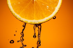 Orange slice and splash of juice isolated on color background