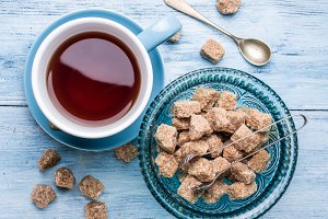 Cup of tea and cane sugar cubes
