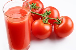 Glass of tomato juice and ripe tomatoes isolated on white