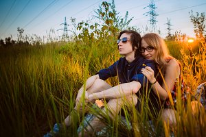 guy and the girl sitting in the grass on a sunset background