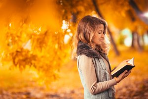 Portrait of a young girl in fur vest and reading book on background autumn park