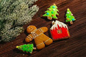 painted gingerbread house, Christmas tree and the man on a wooden background
