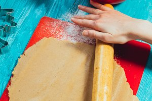 girl rolls the dough on the red board to blue wooden table