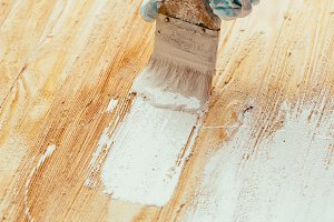 closeup hand use brush paint white on wood surface