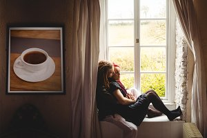 Hipster couple in front of window