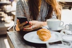 girl using smartphone on cafe