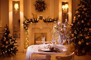 Dinner table in great apartments with decorated Christmas trees