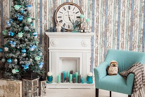 Christmas tree in living room with fireplace, armchair and wallpaper