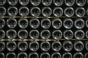 Old bottles of wine in rows in wine cellar. Rows of many wine bottles in winery cellar storage. Beautiful texture or background. Close up