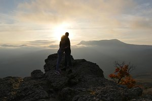 Silhouettes of young couple standing on a mountain and looking to each other on beautiful sunset background. Love of guy and girl.