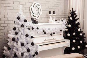Black and White Christmas tree near white piano